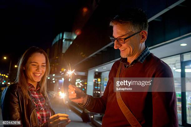Smiling couple holding Christmas sparklers  at night outside