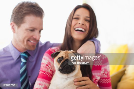 Smiling couple holding cute, small dog : Foto de stock