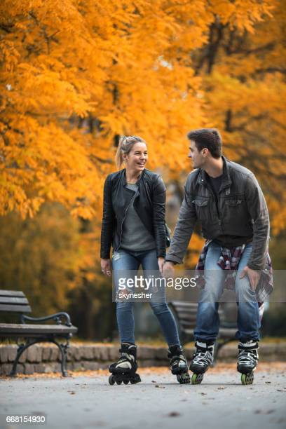 Smiling couple holding hands and roller skating in autumn.