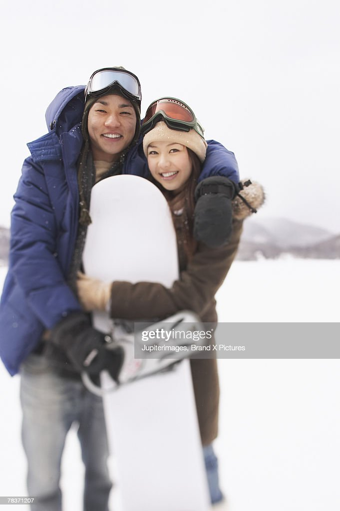 Smiling couple holding snowboard : Stock Photo