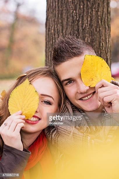 Souriant couple tenant des feuilles devant leurs yeux.