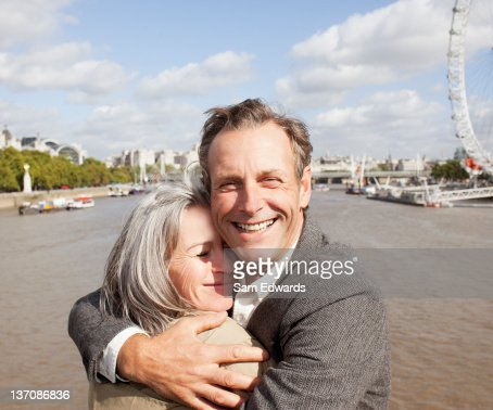 Smiling couple hugging along the Thames river in London : Stock Photo