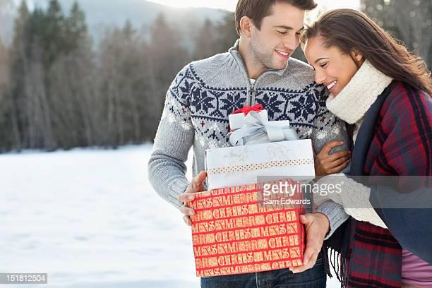 Sonriente pareja abrazándose y la celebración de Navidad y regalos en la nieve