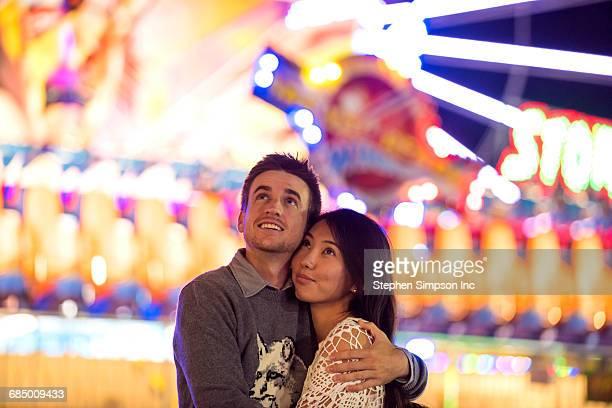 Smiling couple hugging in amusement park