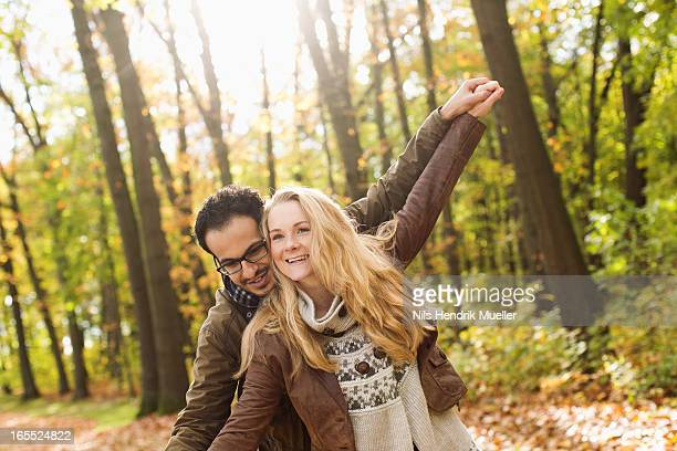 Smiling couple hugging in forest