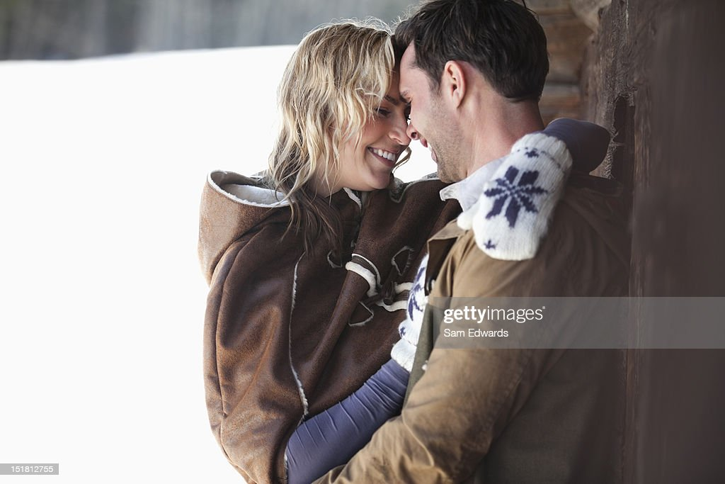Smiling couple hugging in snow : Stock Photo