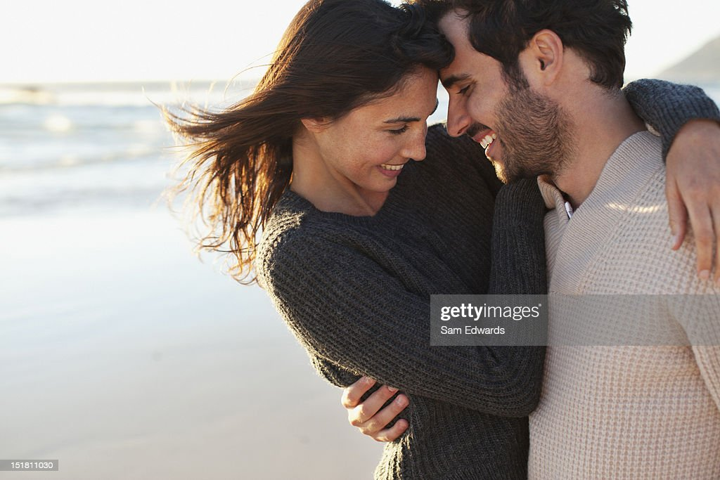 Smiling couple hugging on beach : Foto de stock