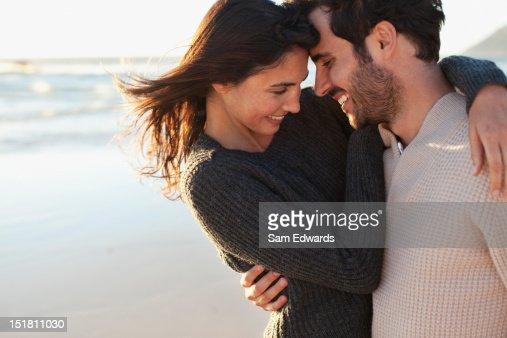 Smiling couple hugging on beach : Foto de stock