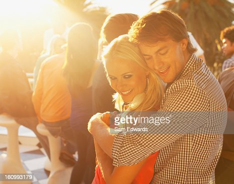Smiling couple hugging on sunny balcony : Stock Photo