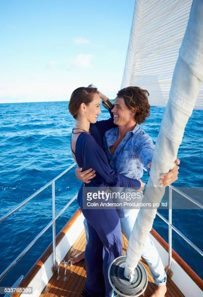 Smiling couple hugging on yacht deck