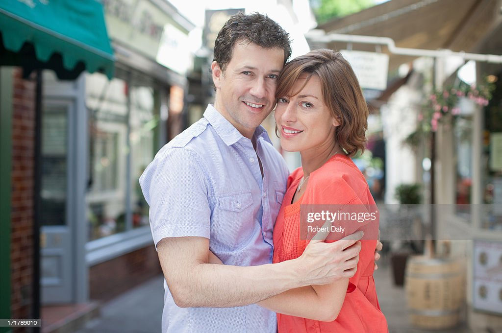 Smiling couple hugging outdoors in town : Stock Photo