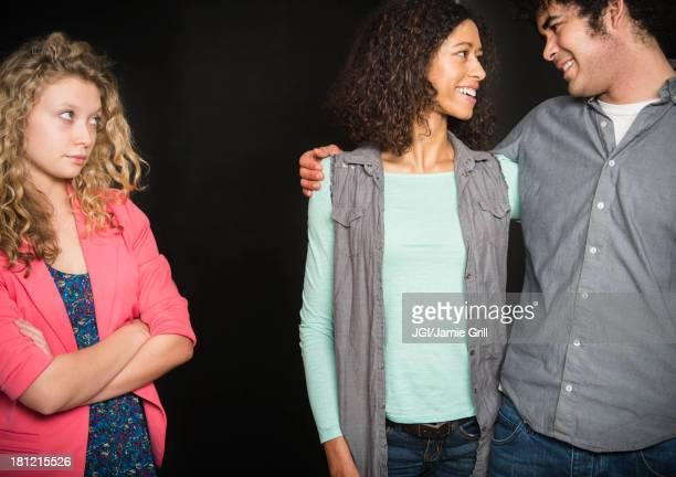 Smiling couple ignoring friend