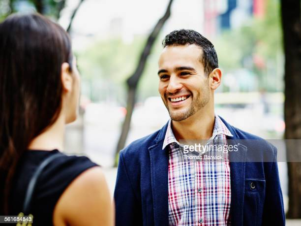 Smiling couple in discussion on city street