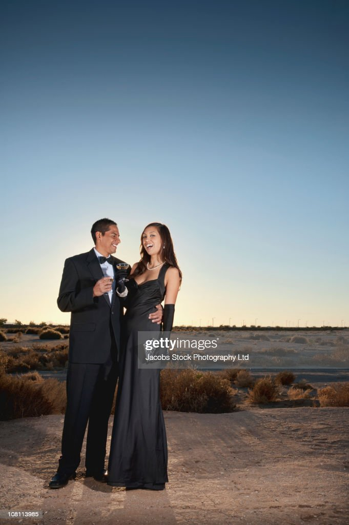 Smiling couple in formal attire drinking champagne in desert : Stock Photo