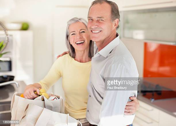 Smiling couple in kitchen with reusable grocery bags