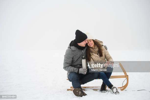 Smiling couple in love sitting on sled