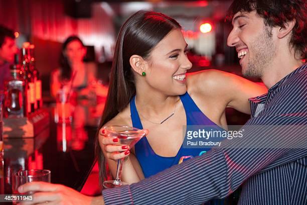 Coppia sorridente in locale notturno con bevande
