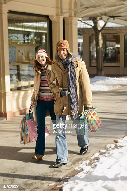 Smiling Couple in Winter Outfits Walk Arm in Arm on the Pavement Carrying Shopping Bags