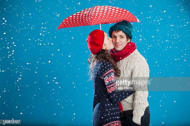 Smiling couple kissing in snow