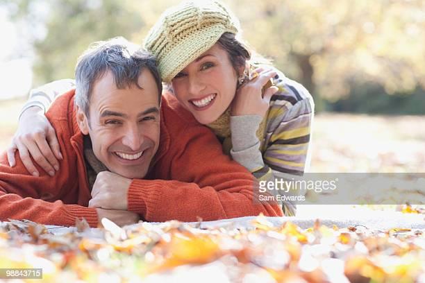 Souriant couple allongé sur les feuilles de l'automne