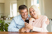 Happy mature couple looking at smartphone together at home in the kitchen