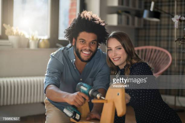 Smiling couple looking at camera mounting rocking horse with cordless drill