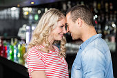 Smiling couple looking at each other in bar