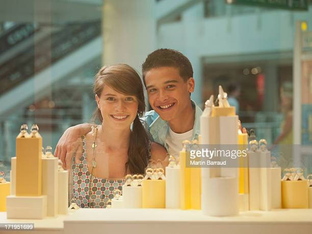 Smiling couple looking at jewelry in display case