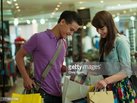 Smiling couple looking in shopping bag in store : Stock Photo
