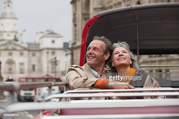Smiling couple looking up on double decker bus in London