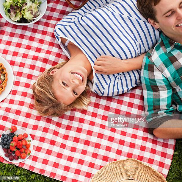 Smiling couple lying on picnic blanket, directly above