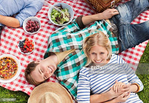 Smiling couple lying on picnic blanket with fruit bowls aside, directly above