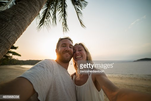 Smiling couple on beach taking selfie