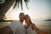 Smiling couple on beach taking selfie