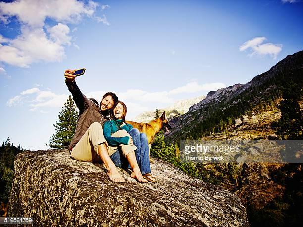 Smiling couple on boulder taking self portrait