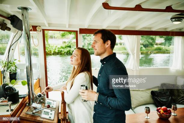 Smiling couple on bridge of boat headed out for cruise on summer evening