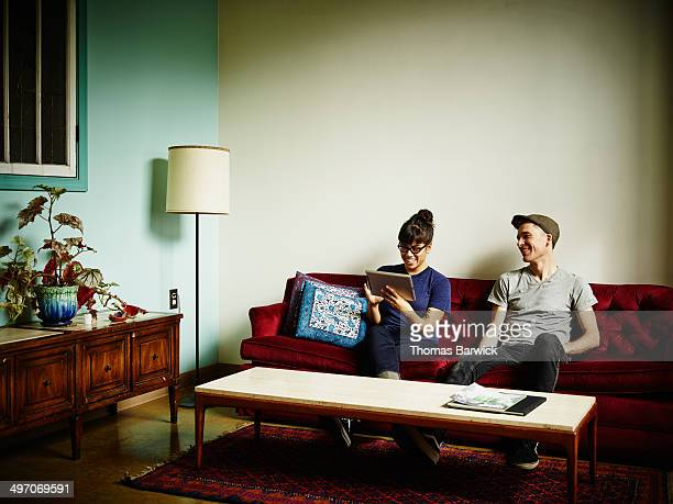 Smiling couple on couch working on digital tablet