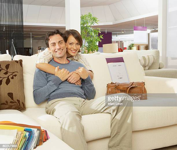 Smiling couple on sofa in furniture shop.