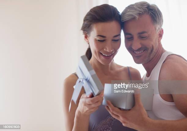 Smiling couple opening gift box