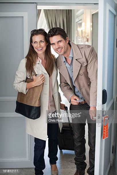 Smiling couple opening hotel room door