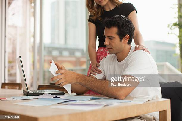 Smiling couple paying bills together