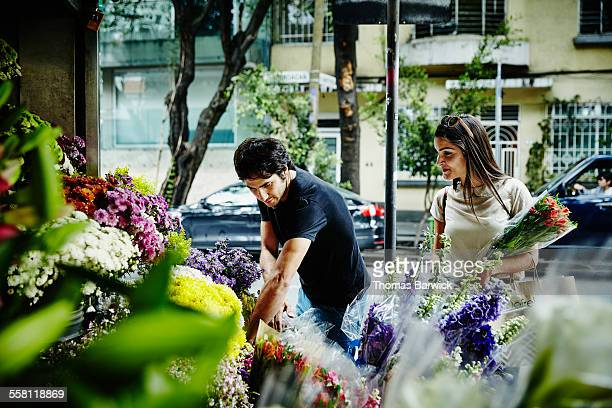 Smiling couple picking out flowers together