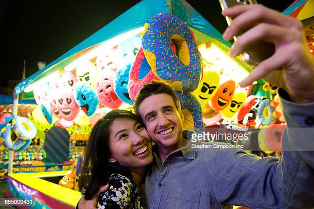 Smiling couple posing for cell phone selfie in amusement park