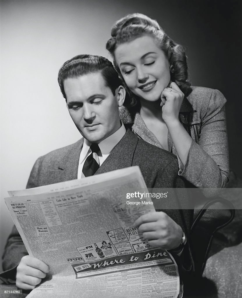 Smiling couple posing in studio, man reading newspaper, (B&W), : Stock Photo