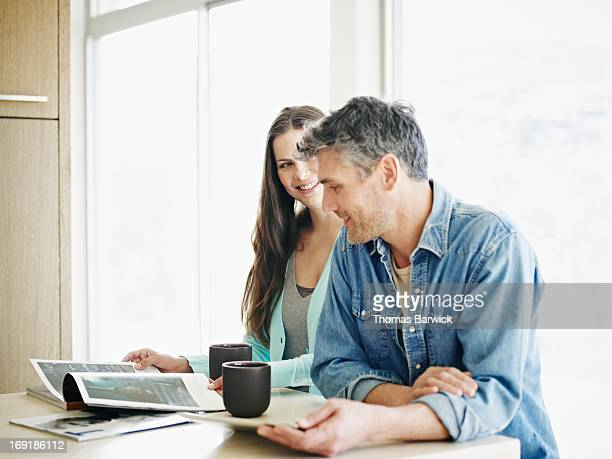 Smiling couple reading at counter in home kitchen