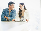Smiling couple reading at counter in home