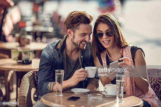 Smiling couple relaxing in a cafe and using smart phone.