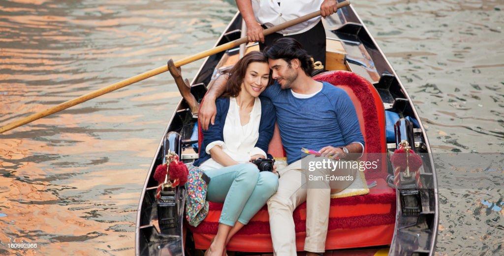 Smiling couple riding in gondola in Venice