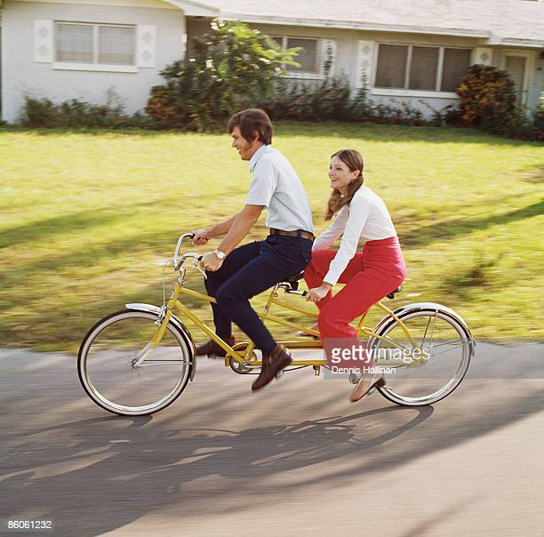 Smiling couple riding tandem bicycle