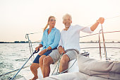 Smiling mature couple sitting on the deck of their boat while enjoying a day together sailing on a sunny afternoon